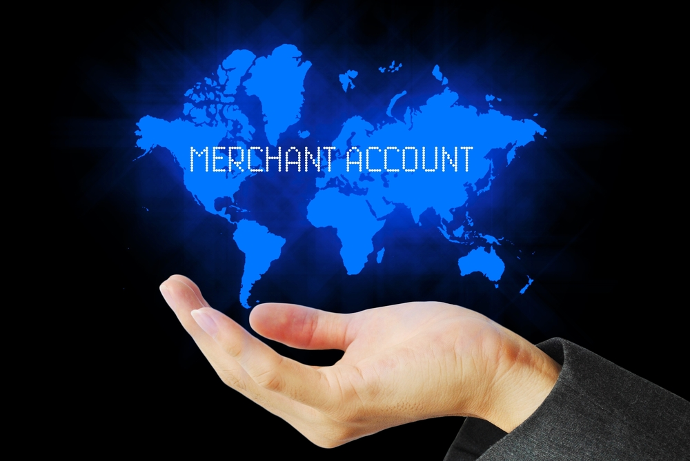 "online merchant account concept -- hand holding map of the world saying ""merchant account"""